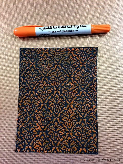 Damask Embossed Black Cardstock Colored Over with Carved Pumpkin Distress Crayon